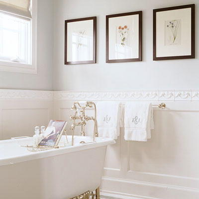 Trois, framed pictures are hung horizontally on the wall above a claw foot tub in a white bathroom