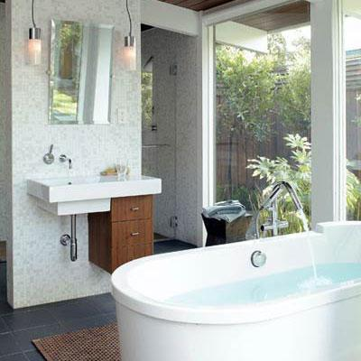 mod style bathroom with a hanging white sink and wooden drawers hung on the lower-right side, below and a stand-alone modern tub in the middle of the room