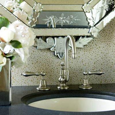 une close up view of a classic bathroom faucet with a decorative patterned mirror behind it and dark countertop