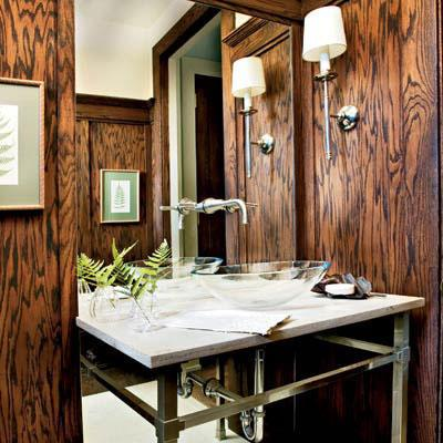 foncé, wood paneling offsets a white marble countertop with a raised glass sink and steel legs in a small bathroom