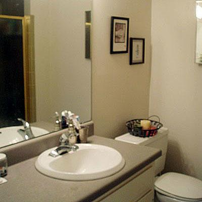 un outdated bathroom with gray formica countertops and a mirror before it is to be renovated