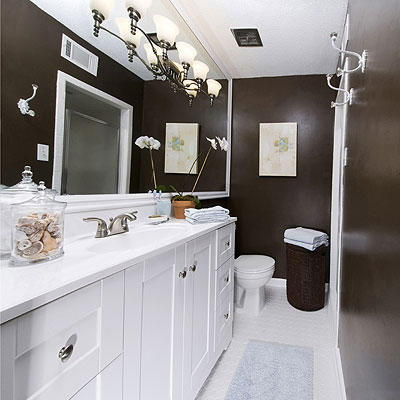 Profond chocolate walls of this renovated bathroom offset the crisp, white bathroom cabinets and the large, expansive bath mirror with a light fixture
