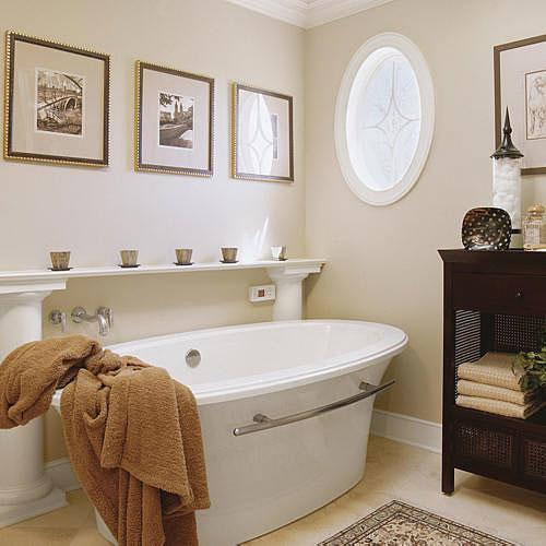blanc, freestanding tub with a classic white shelf held up by neoclassical columns rises above the tub and an oval window with frosted glass pattern is on the wall across from the tub