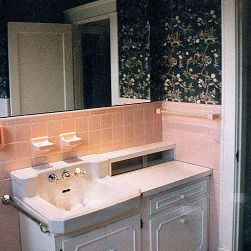 une before photo of a bathroom with pink tile around the sink area and dark, black flowered wallpaper