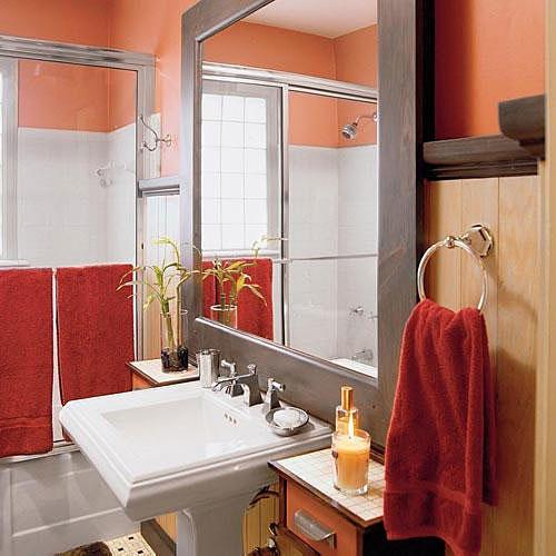 un oversized mirror with a dull metal frame brings in a ton of reflected light to a small bath that's decorated in peach, and ruby tones with natural, beaded-wood walls and a white pedestal sink