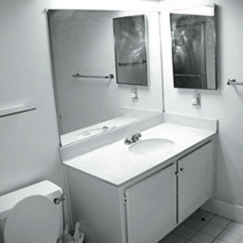 noir and white photo of a plain bathroom with a sink in a simple cabinet with a wall mirror above