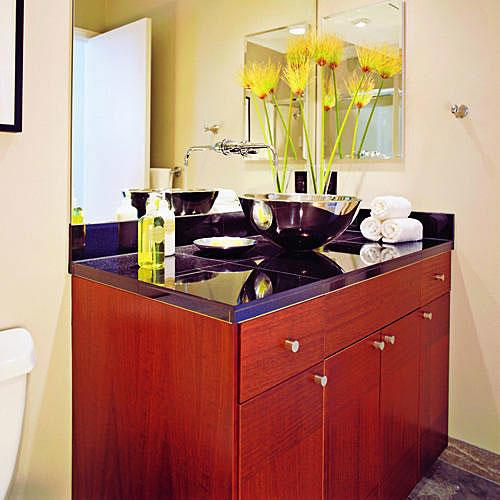 une stainless steel vessel sink sits on top of black granite sink counter top with cherry wood kitchen-cabinet base below in this teen's bathroom