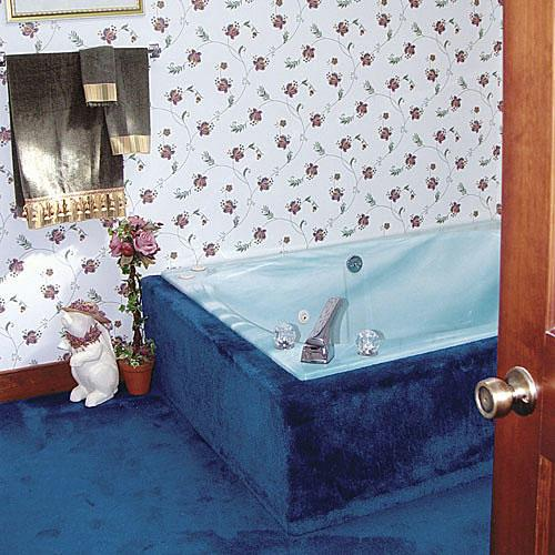 brillant blue carpet runs up along the sides of the tub and outdated wallpaper with small flowers off-sets this dated master bathroom